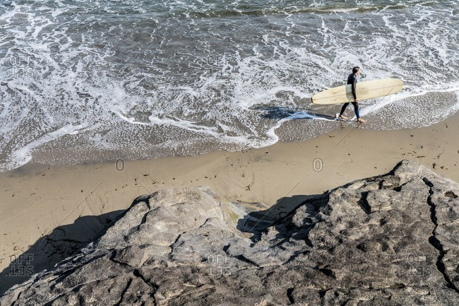Surfer walks along the beach near Santa Cruz, California