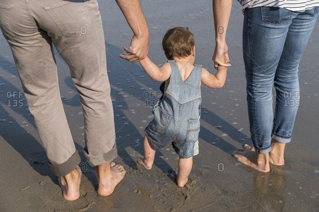 Baby boy walks with his parents on the beach