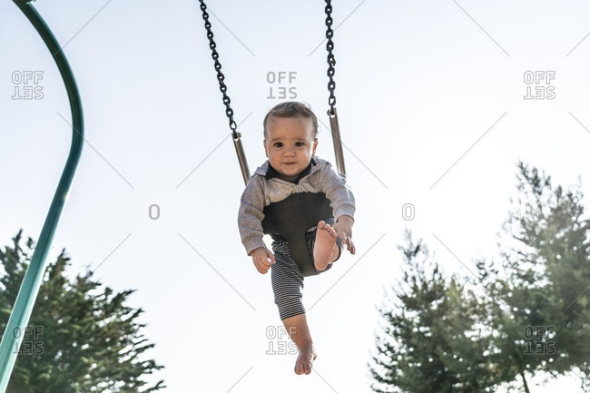 10 month old baby boy sitting on a playground swing