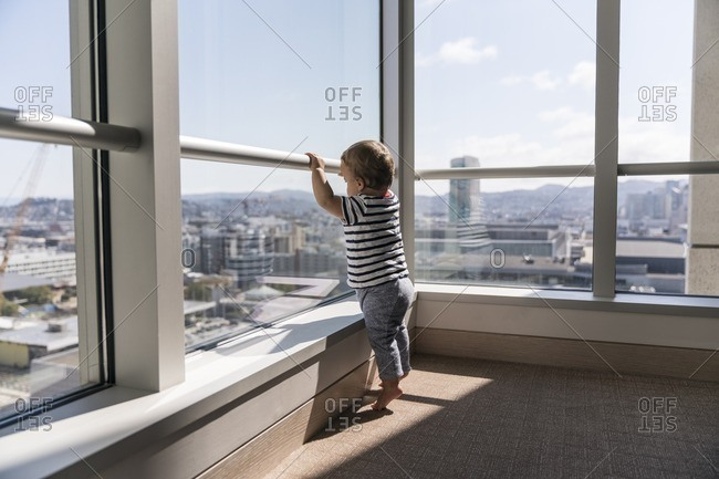 10 month old baby boy standing on tip toe to see out a window in a high-rise building
