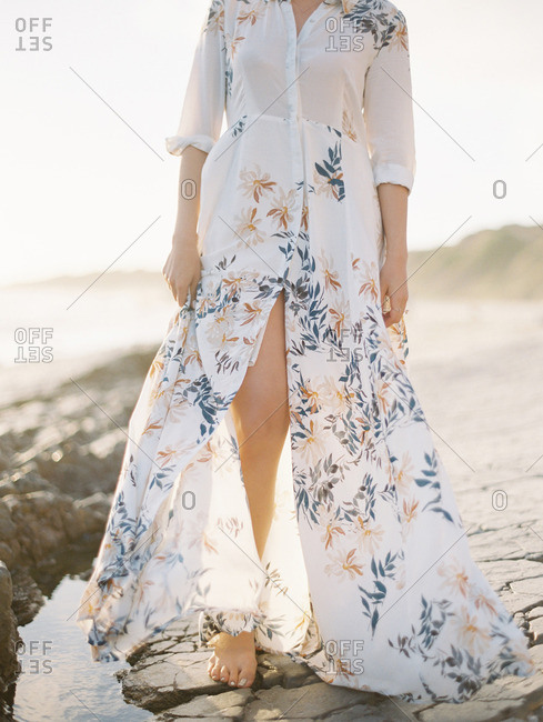 Woman wearing a floral print dress standing on a beach