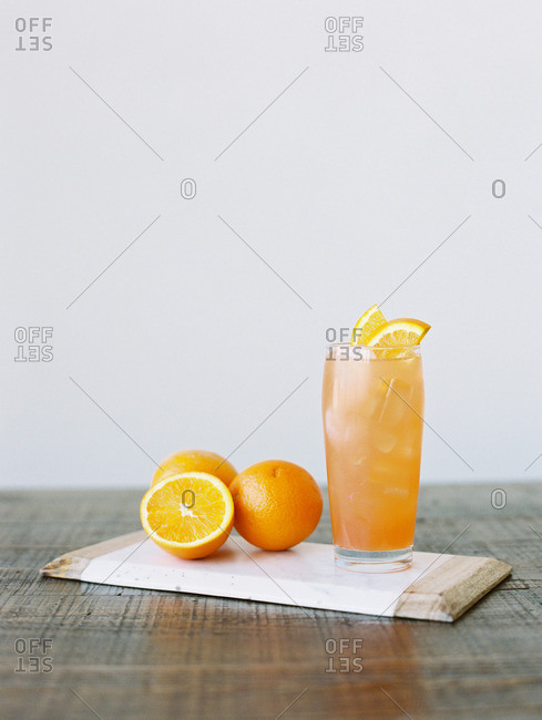 Orange juice drink on a cutting board beside cut oranges