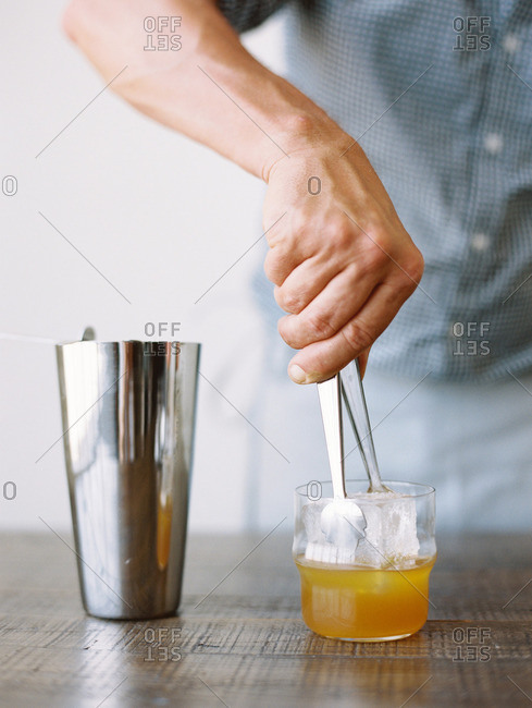 Man placing an ice cube in a drink