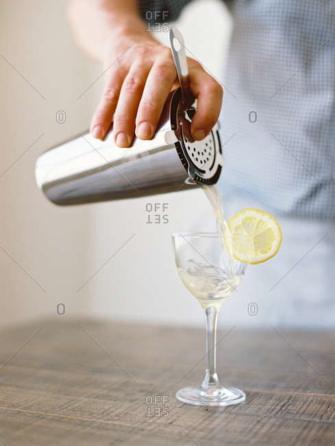Man pouring a beverage from a cocktail shaker and strainer set