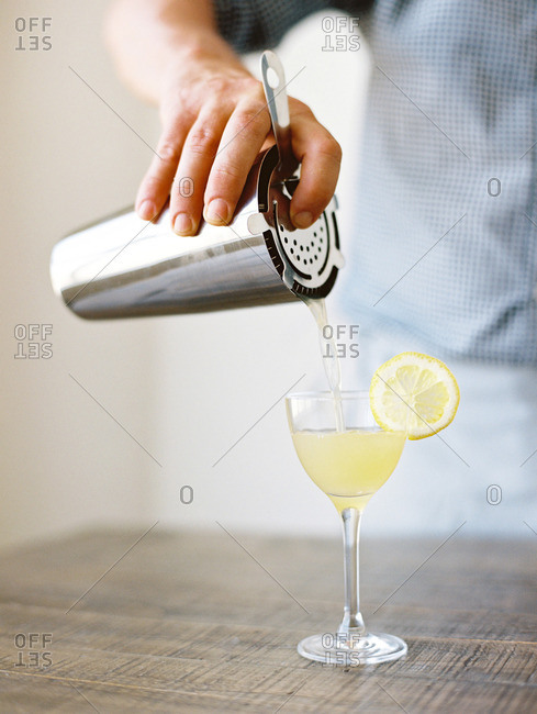 Man pouring a drink from a cocktail shaker and strainer set