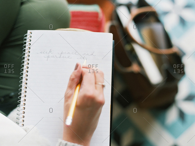 Overhead view of a woman writing notes in a notebook