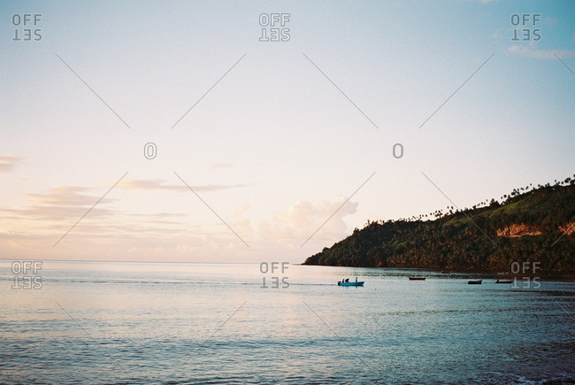 Boats anchored along a secluded island cove at sunset