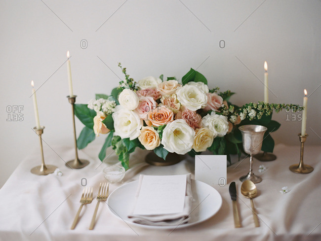 A table set with a bouquet of flowers, candles, and dinnerware