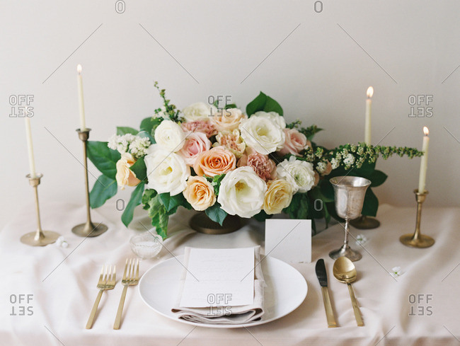 A table setting comprised of a bouquet of flowers, candles, plate and silverware