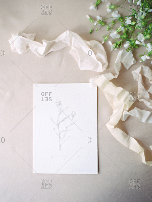 A table set with flowers, ribbon, and a note card