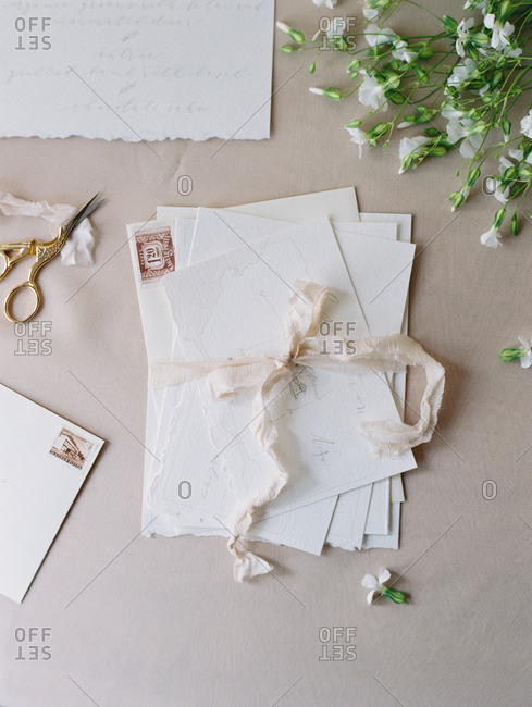 A table set with flowers, ribbon, scissors, and a bundle of note cards