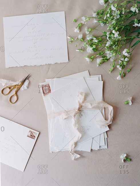 A table set with flowers, ribbon, scissors, and a bundle of invitations