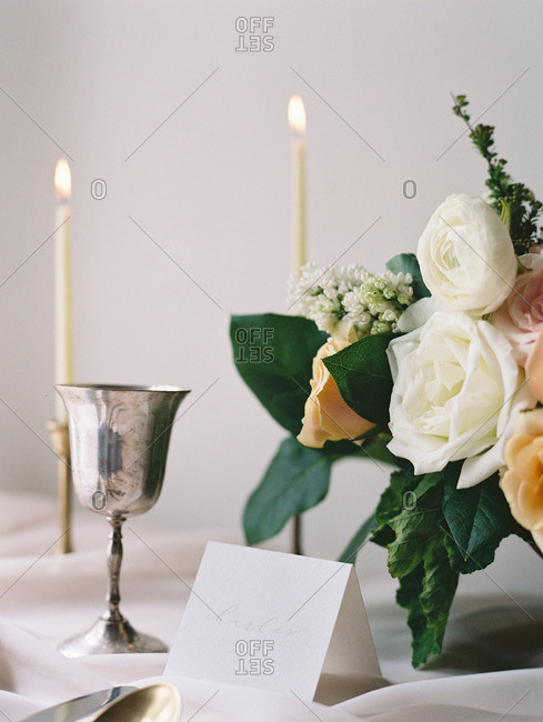 A table set with a bouquet of flowers, candles, plate and silverware