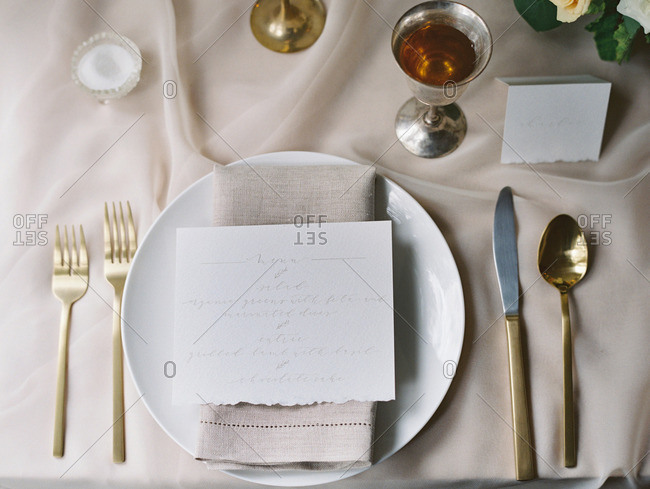 A table set with a bouquet of flowers, candles, menu, and dinnerware