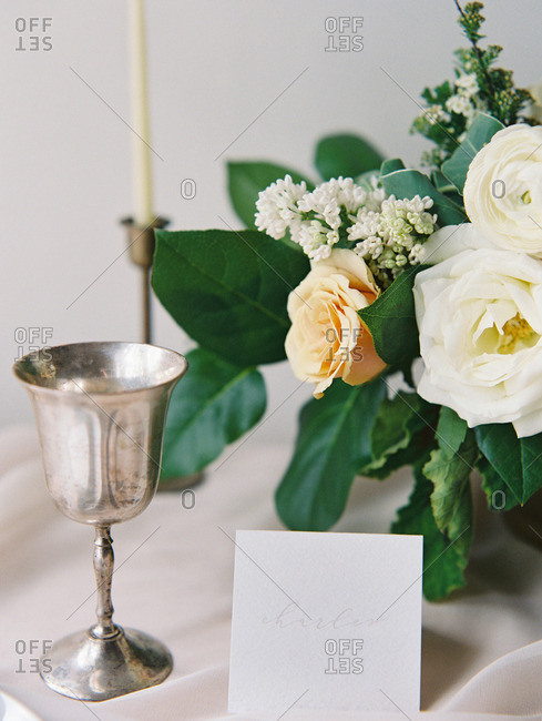 A table set with candles, goblet, and a card