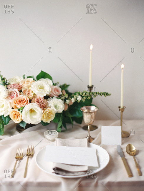 A table set with flowers, candles, menu, and dinnerware