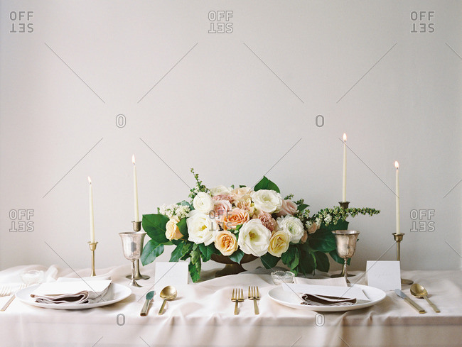 Table set with flowers, candles, menu, and dinnerware