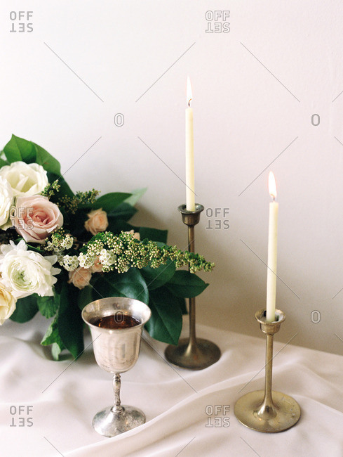A table set with candles, goblet, and a bouquet of flowers