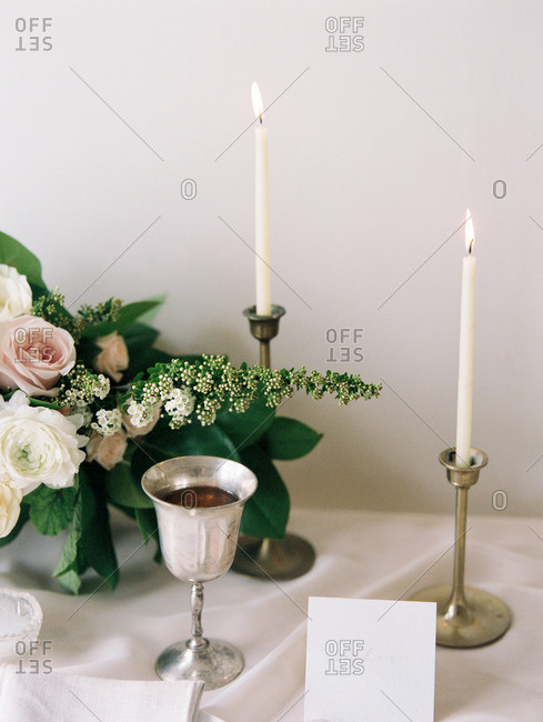 A table set with candles, card, goblet, and a bouquet of flowers