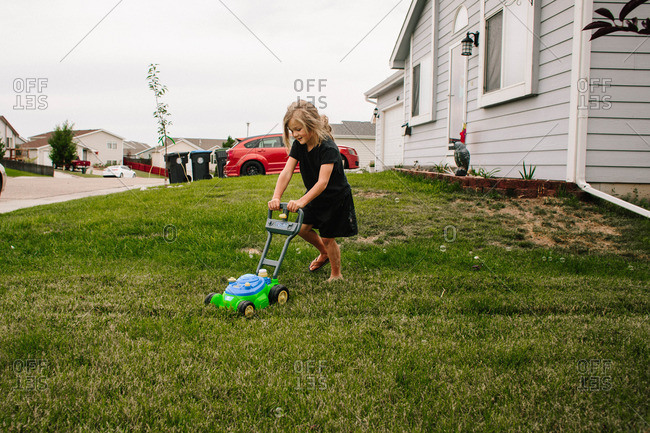 Boy pushing a toy lawn mower on the front lawn
