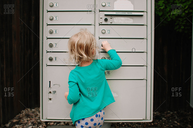 Toddler child trying to open a mailbox