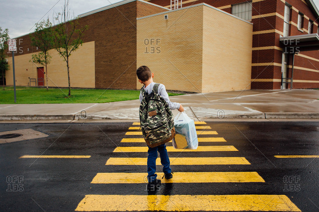 Boy wearing a backpack walking through a crosswalk on the way to school