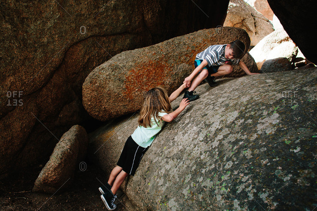 Boy helping to pull another boy up onto a large boulder