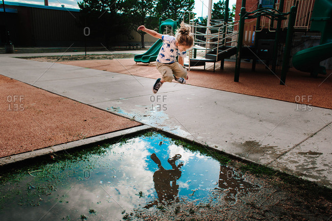 Little boy about to jump into a puddle on the playground