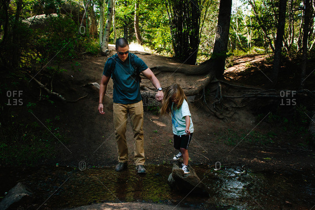 Father helping son cross a creek while hiking in the forest