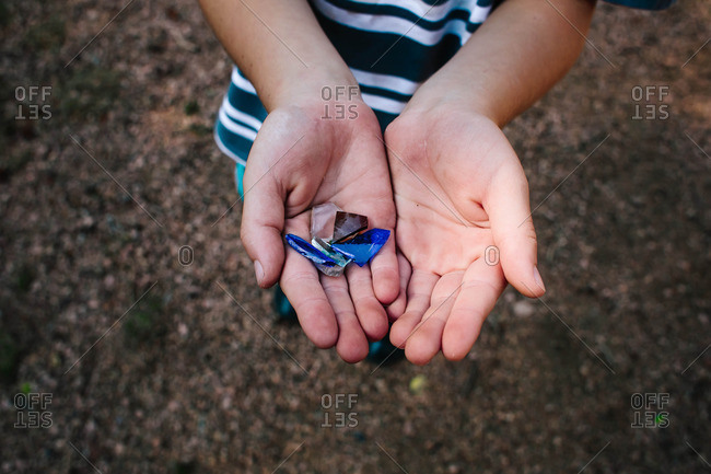 Child holding pieces of broken glass