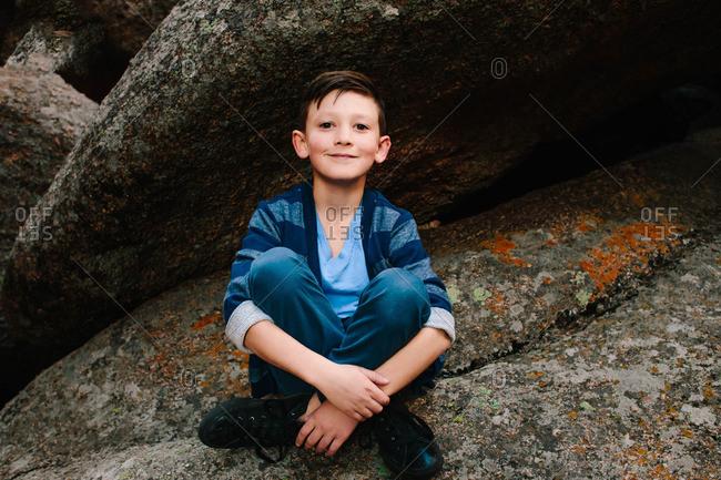 Portrait of a boy sitting cross legged on a boulder