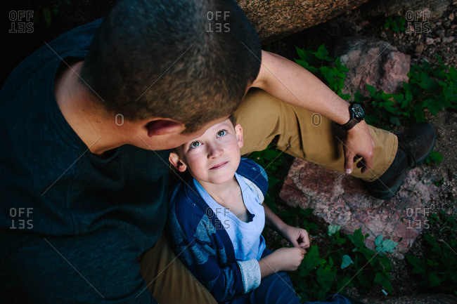 Boy looking up at his father while sitting together on rocks