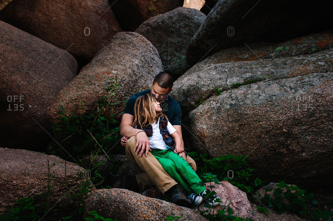 Father holding his son while sitting together on a boulder