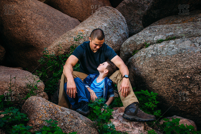 Father and son making silly faces at each other while sitting together on a boulder