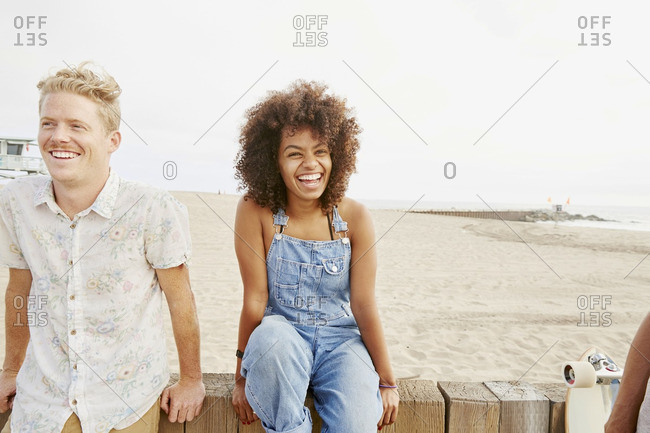 Portrait of two friends sitting against a wood fence