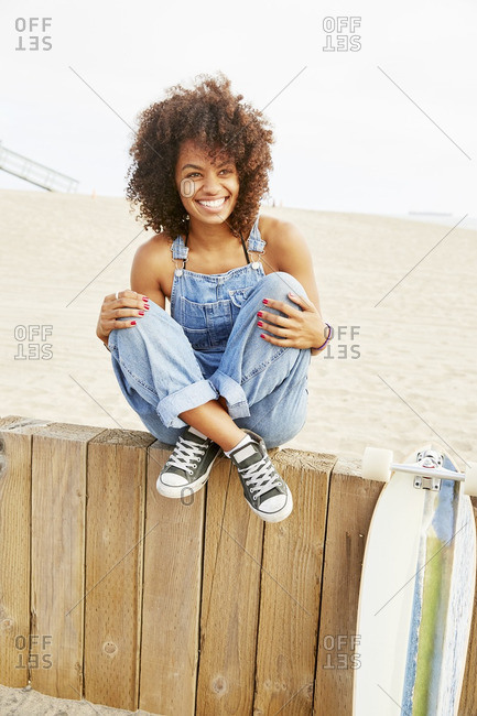 African American woman sitting on a wood fence at the beach