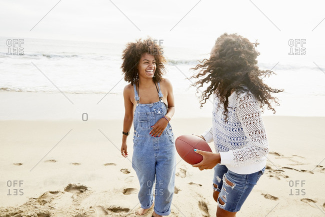 Two women playing football on the beach