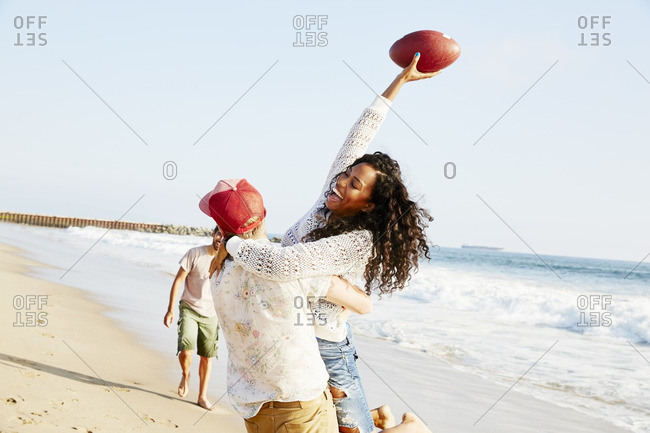 Friends playing football on the beach together