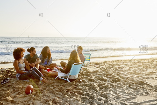 Friends sitting together on a beach at sunset