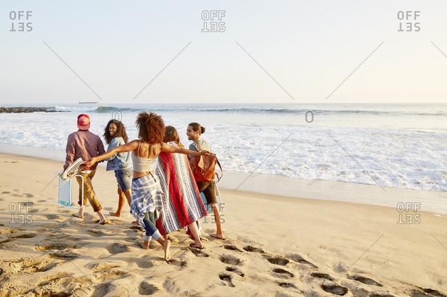 Friends walking together along a beach