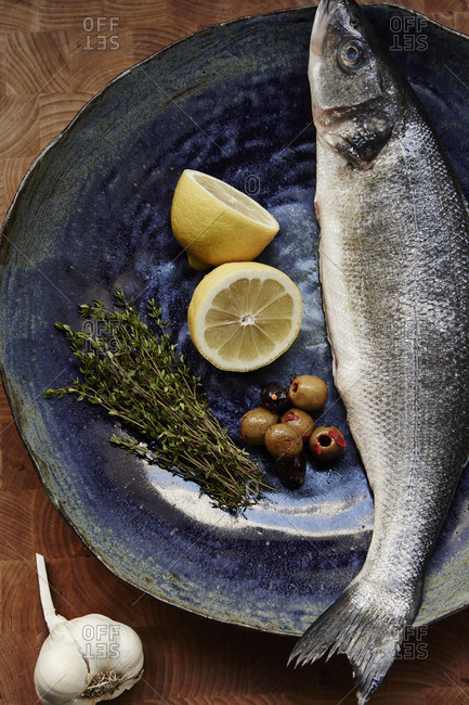 Branzino with herbs and olives on a stoneware plate