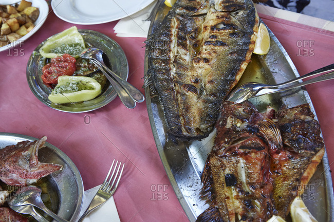 A meal of grilled fish with sides of vegetables on silver platters
