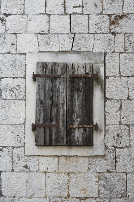 Close up of an old window with wooden shutters and rusted hardware