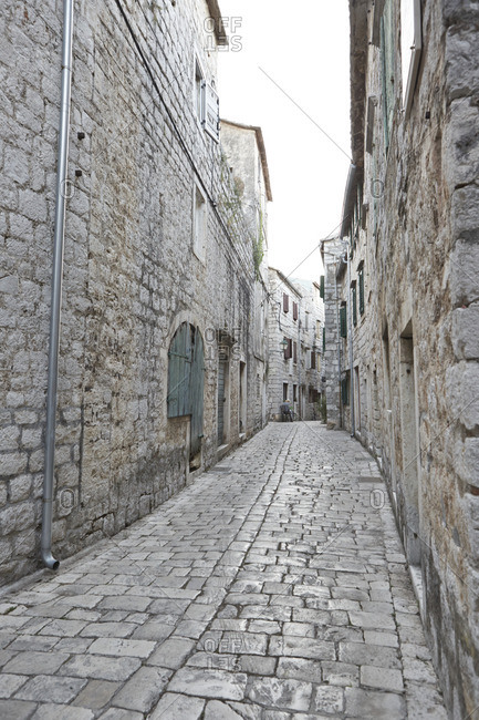 A small historic side street featuring a winding cobblestone path