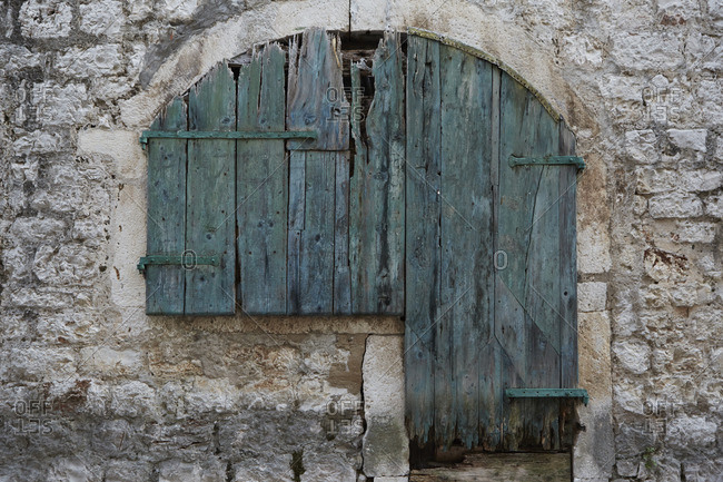 Close up of a colorful and odd shaped window with wooden shutters and rusted hardware