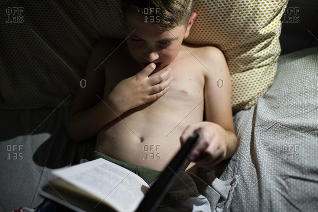 Boy in bed reading a book