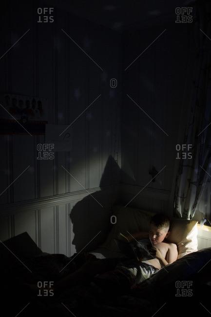 Boy sitting in a dark room reading a book