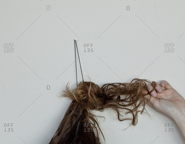 A woman pulling her hair while standing against a white wall
