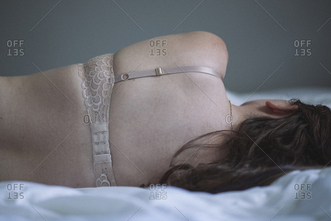 Woman wearing a bra lying on a bed