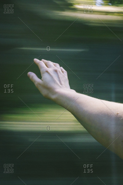 Arm extended against a blurred background